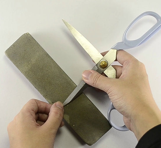 To sharpen plain, household scissors that are very dull, start by using the coarse side of a bench stone. Simply open the scissors and place the edge to be sharpened on the stone. Pull the blade toward you from one end of the stone to the other while maintaining contact with the stone.